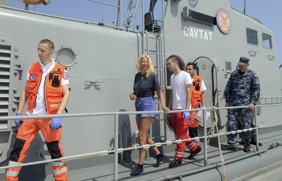 A turista britânica de 46 anos (de short e camiseta) é escoltada pelos croatas que a resgataram (Foto: AP Photo)