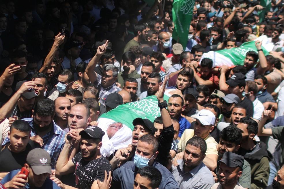 Palestinos carregam corpos de militantes do Hamas em 13 de maio de 2021  — Foto: Mohammed Salem/Reuters