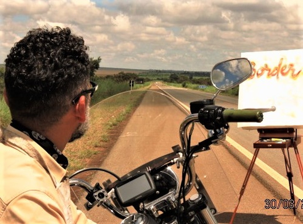Brasiliense de moto em estrada com quadro de pintura: ele vai até o Alasca para pintar pessoas pelo mundo — Foto: Carlos Bueno/TV Globo