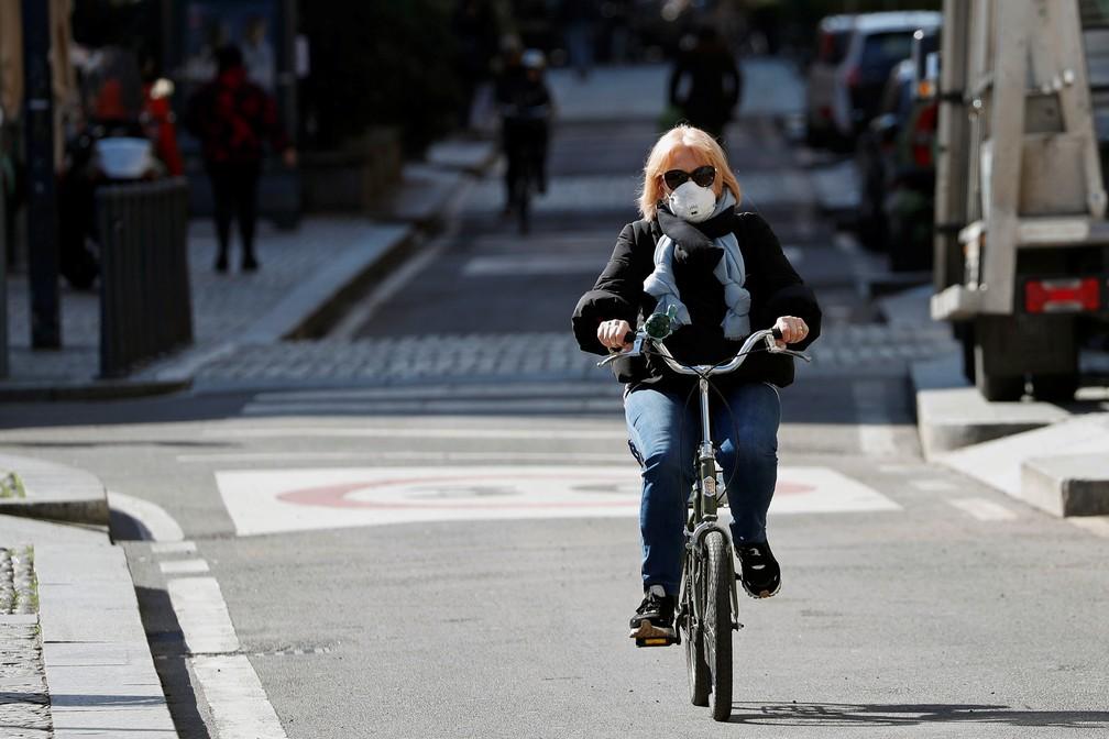Mulher usa máscara contra o novo coronavírus enquanto anda de bicicleta em Milão, no norte da Itália, nesta quarta (4). — Foto: Guglielmo Mangiapane/Reuters