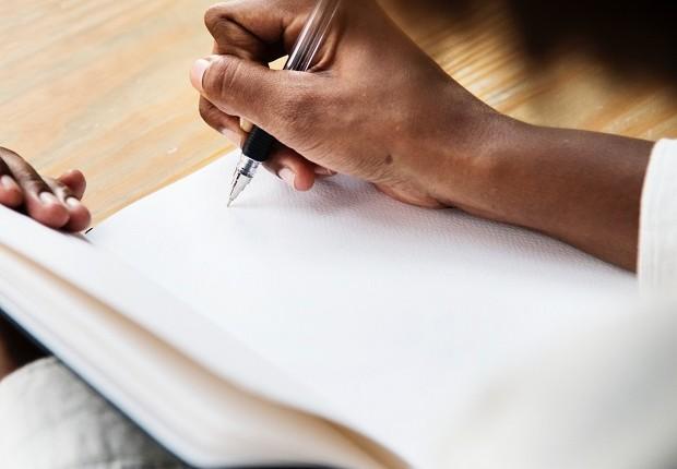 Mulher escreve em caderno (Foto: Pexels)