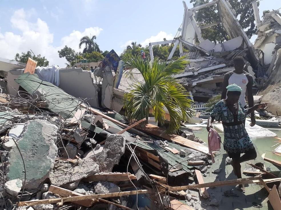 Pessoas caminham entre escombros de casas destruídas pelo terremoto em Les Cayes, no Haiti — Foto: Jose Flecher/cortesia via Reuters