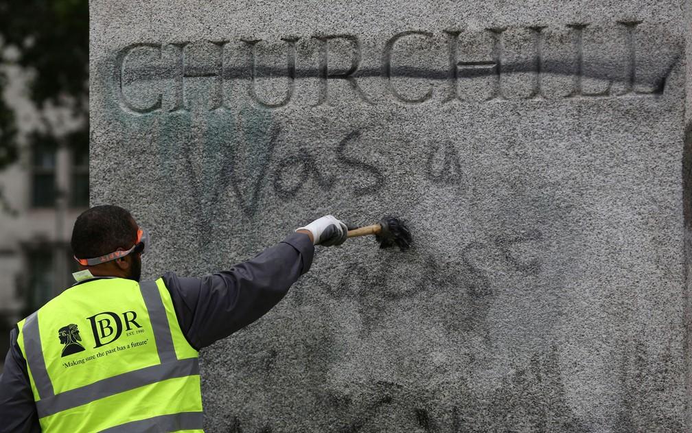 Funcionário limpa pichação da estátua de Sir Winston Churchill na Parliament Square, em Londres, na segunda-feira (8) — Foto: Aaron Chown/PA via AP