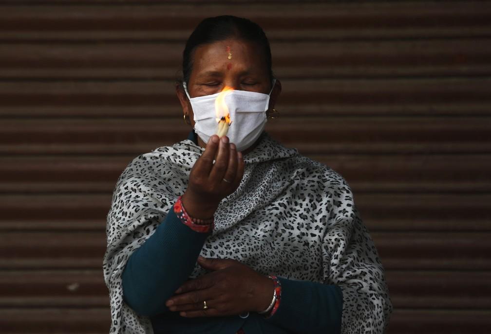 9 de abril - Devota é vista orando durante o festival 'Rato Machhindranath', em Lalitpur, Nepal, nesta quinta-feira (9). Devido ao bloqueio para impedir a propagação do novo coronavírus, apenas um pequeno número de pessoas participou do festival, frequentado por milhares todos os anos — Foto: Niranjan Shrestha/AP