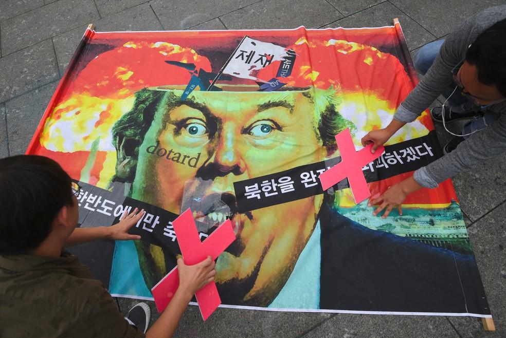 Ativistas anti-guerra finalizam um cartaz com uma caricatura do presidente Donald Trump durante uma manifestação contra ele perto da embaixada dos EUA em Seul, na Coreia do Sul. A mensagem na bandeira diz 'Se a guerra explodir, apenas aqueles na península coreana morrerão', e 'destruirá totalmente a Coreia do Norte' (Foto: Jung Yeon-Je/AFP)