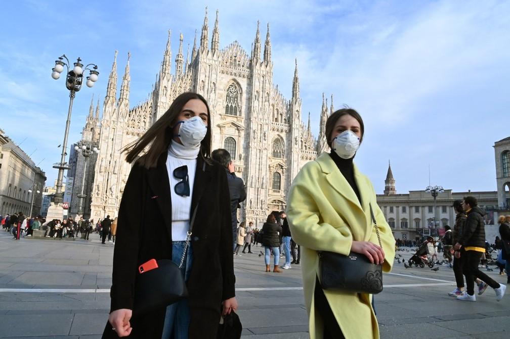 Mulheres usam máscaras para se proteger do coronavírus na praça da catedral de Milão, na Itália, em 23 de fevereiro de 2020 — Foto: Andreas Solaro / AFP