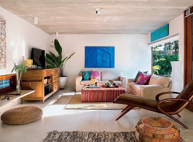 O interior da casa projetada pelo escritório Brasil Arquitetura tem acabamentos e móveis simples. O piso de cimento branco queimado reveste todos os cômodos. A cor – o azul do mar – fica por conta dos quadros (Foto: Edu Castello/Casa e Jardim)