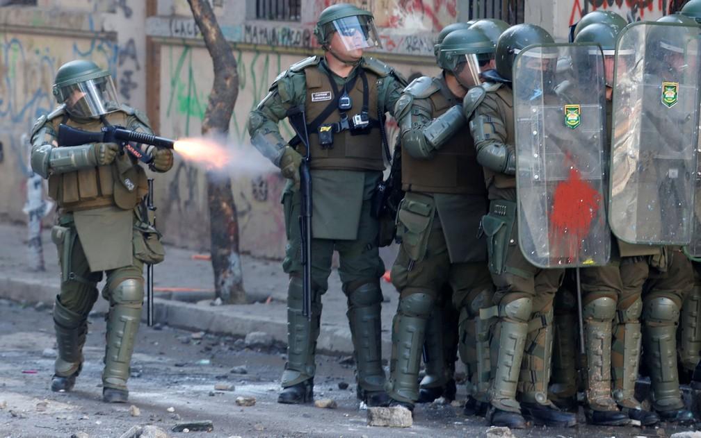 Membro de forças de segurança dispara gás lacrimogêneo contra manifestantes em Santiago, no Chile, no sábado (16) — Foto: Reuters/Goran Tomasevic
