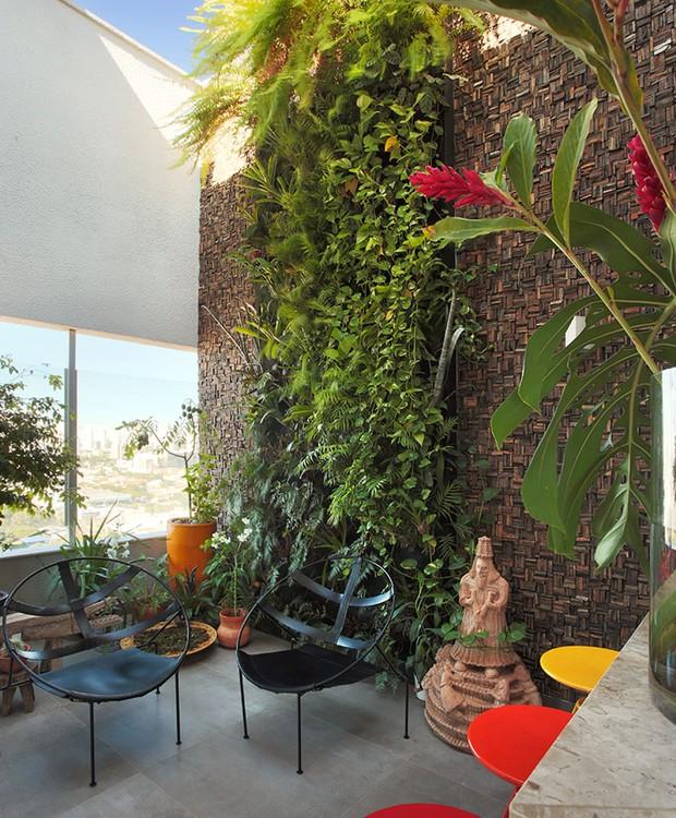 No pavimento superior, a cascata de plantas fica emoldurada por um revestimento de pedras filetadas. Cadeiras de Flavio de Carvalho recebem os visitantes (Foto: Paulo Rezende)