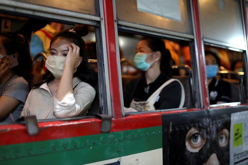 9 de março - Mulheres são vistas em um ônibus utilizando máscaras de proteção devido ao surto do novo coronavírus covid-19 em Bangkok, na Tailândia — Foto: Jorge Silva/Reuters