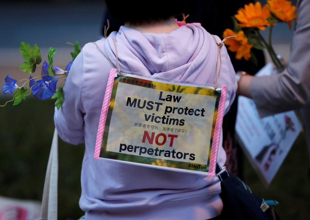 """Manifestante contra a lei antiestupro do Japão leva cartaz escrito com """"a lei deve proteger as vítimas, não os perpetradores"""" em protesto desta terça-feira (11) em Tóquio. — Foto: Issei Kato/Reuters"""