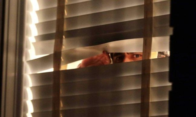 Fotografia da casa de Aécio Neves mostra um homem olhando pela janela: imagem foi atribuída, equivocadamente, ao senador tucano; era um de seus assessores (Foto: Luis Nova / Esp. CB)