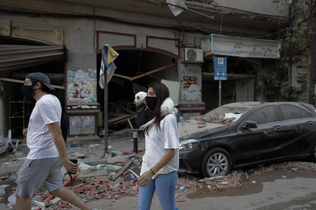 5 de agosto - Pessoas passam por prédios danificados após explosão em Beirute, Líbano — Foto: Hassan Ammar/AP
