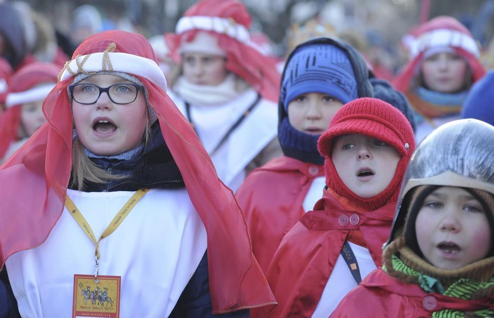 Alunos cantam durante as celebrações da Epifania em dia com temperatura de -12ºC, em Varsóvia, na Polônia (Foto: AP Photo/Alik Keplicz)