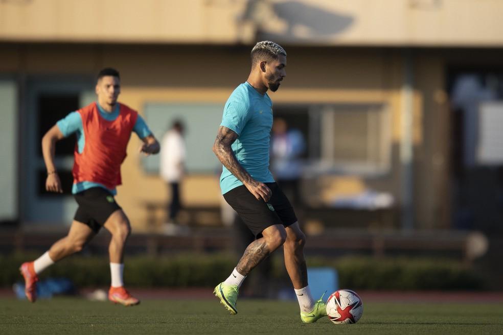 Douglas Luiz controla a bola no treino da seleção olímpica. Ao fundo, Paulinho acompanha a jogada — Foto: Lucas Figueiredo / CBF
