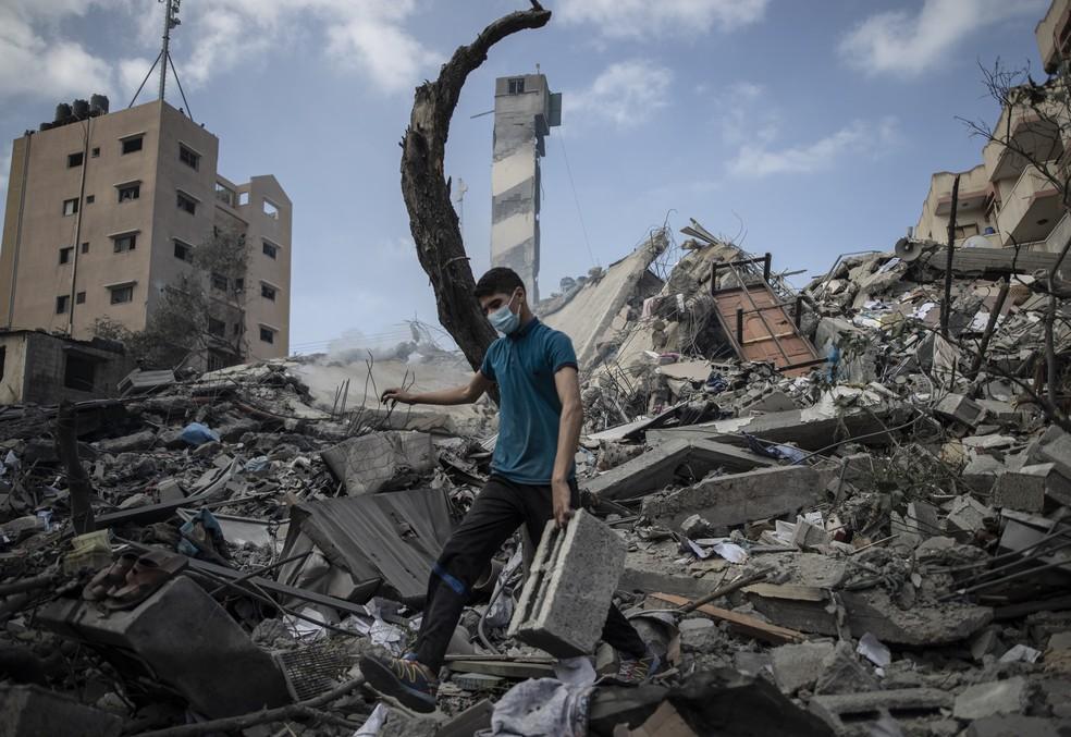 Palestino caminha sobre os destroços de prédio de 6 andares bombardeado por Israel no dia 18 de maio de 2021 — Foto: Khalil Hamra/AP