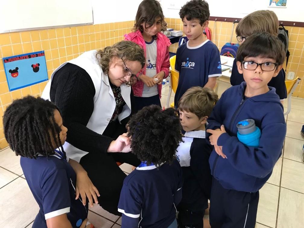 A professora Cynthia Rosal cola esparadrapos nas crianças da turma de Miguel Gadelha ao menos duas vezes por semana (Foto: Ana Luiza de Carvalho/G1)
