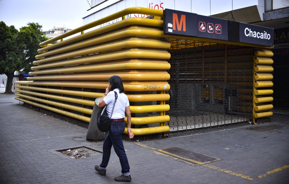Pedestre passa ao lado de metrô fechado durante apagão nesta terça-feira (26) — Foto: Yuri Cortez/AFP