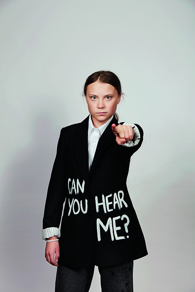 Cover feature of activist Greta Thurnberg. She is wearing a black suit and white shirt with her hair tied back. The suit jacket that says 'Can you hear me?' across the front in white capital letters, and she is pointing at the camera. (Foto: © Christopher Hunt)