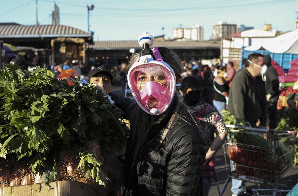 2 de abril - Uma cliente usa uma máscara de snorkel como precaução contra a disseminação do novo coronavírus no mercado de La Vega, em Santiago, no Chile — Foto: Esteban Felix/AP