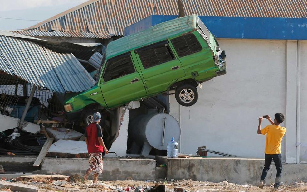 Rapaz tira foto de um carro erguido pelo tsunami — Foto: Tatan Syuflana / AP
