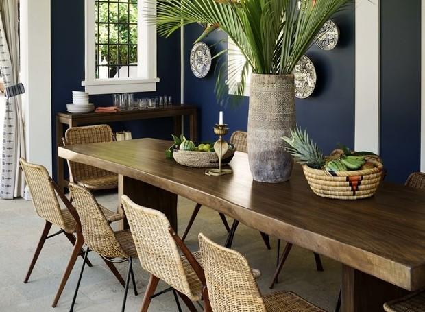 Do lado de fora, uma mesa de madeira e cadeiras de palha trançada trazem aconchego ao ambiente  (Foto: Douglas Friedman/ Reprodução)