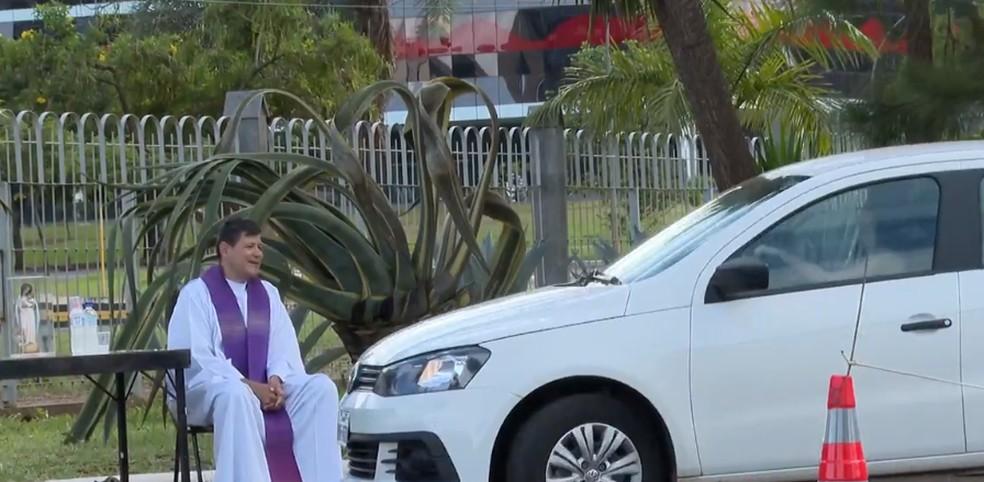 Padre recebendo fiéis por meio de atendimento drive-thru no DF — Foto: Reprodução TV Globo
