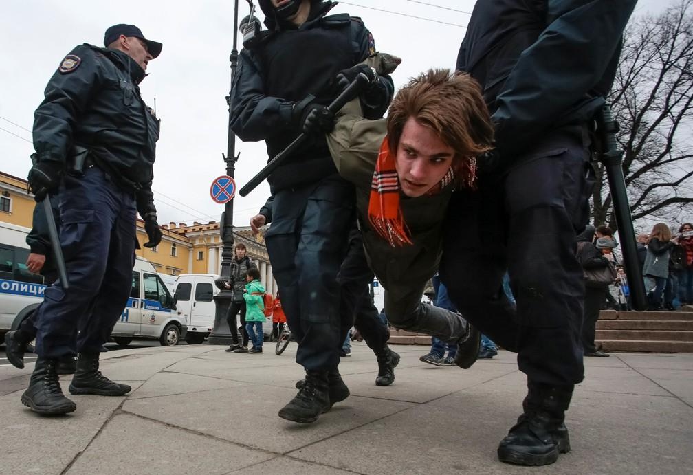 Um manifestante é detido por policiais durante um protesto contra o presidente Vladimir Putin em São Petesburgo, na Rússia, neste sábado (Foto: Anton Vaganov/Reuters)