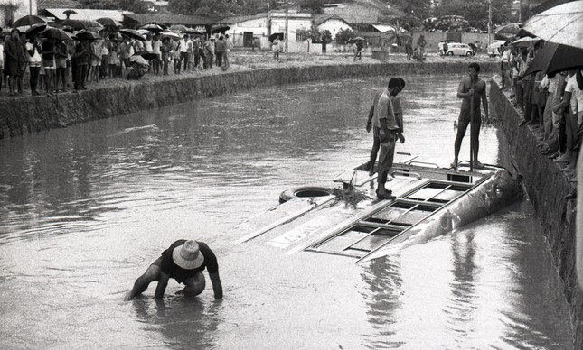 Voluntários ajudam passageiros a sair de ônibus que caiu no rio em Braz de Pina