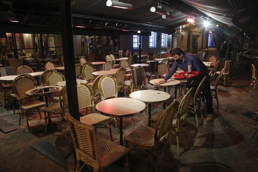 Garçom limpa mesa de bistrô em Paris, na França, em 16 de outubro de 2020. Novas restrições forçaram restaurantes, cinemas e teatros a fechar na capital francesa devido a um toque de recolher para frear o avanço da segunda onda do novo coronavírus. — Foto: Michel Euler/AP