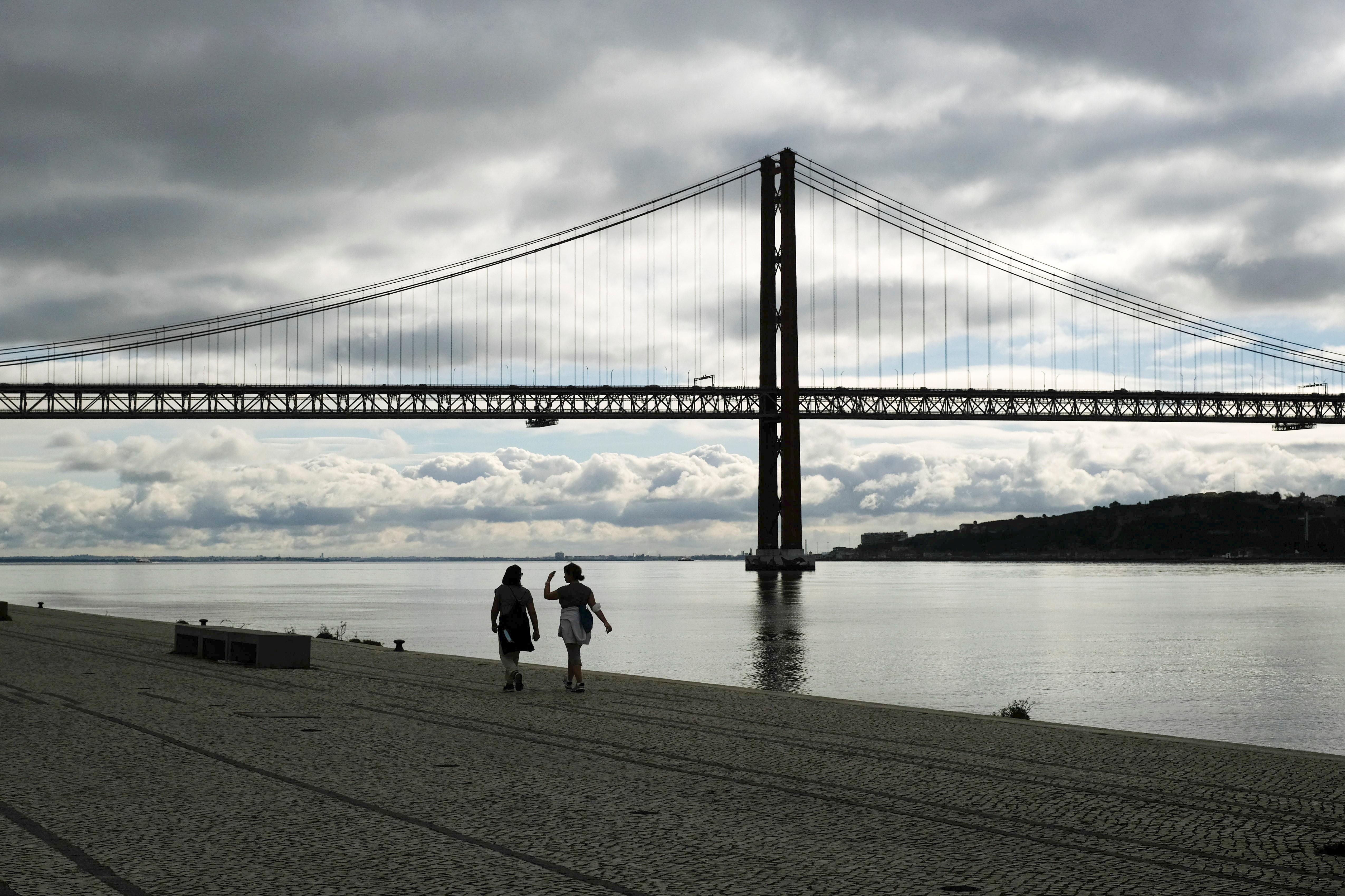 Pessoas caminham à beira do Rio Tejo, em Lisboa