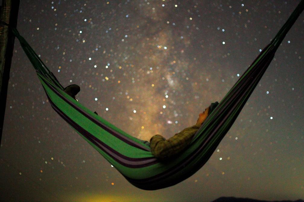 Jovem observa o céu, com a Via Láctea vista ao fundo, durante chuva de meteoros Perseidas durante a madrugada em Kozjak, na Macedônia — Foto: Ognen Teofilovski/Reuters