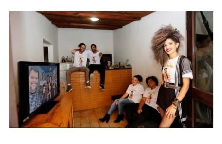 A família de Babu Santana na sala de sua casa. O ator aparece na TV. Ali ele faz lives para as redes sociais na quarentena Editora Globo