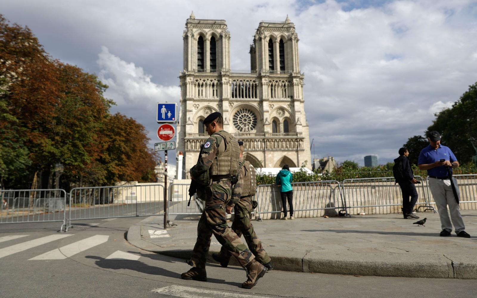 Soldados evacuam área ao redor da Catedral de Notre-Dame, em Paris, antes do início dos trabalhos de limpeza do chumbo no local, na segunda-feira (12) — Foto: AP Photo/Lewis Joly