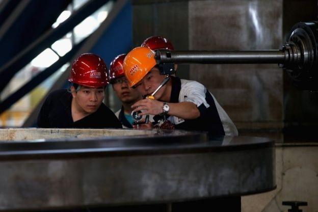 Operários chineses examinam equipamento de mineração em Shenyang; país é referência em reuso de rejeitos de mineração (Foto: Getty Images via BBC News)