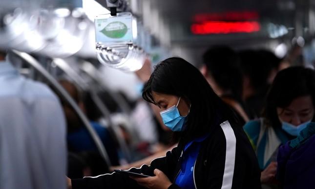 Mulher usando máscara usa o celular em Pequim