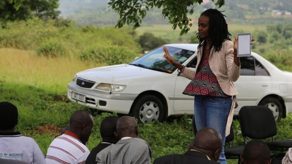 Dr. Nakalembe fala a fazendeiros sobre como usar um aplicativo para enviar informações sobre as plantações — Foto: Catherine Nakalembe via BBC