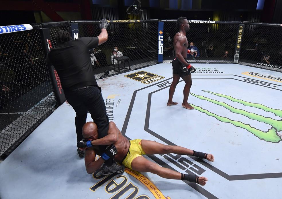 Anderson Silva agarrou-se às pernas do árbitro Herb Dean após ser nocauteado por Uriah Hall — Foto: Getty Images