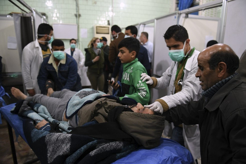 Homem sírio é levado para tratamento em hospital controlado pelo regime de Aleppo, neste sábado (24) — Foto: GEORGE OURFALIAN / AFP