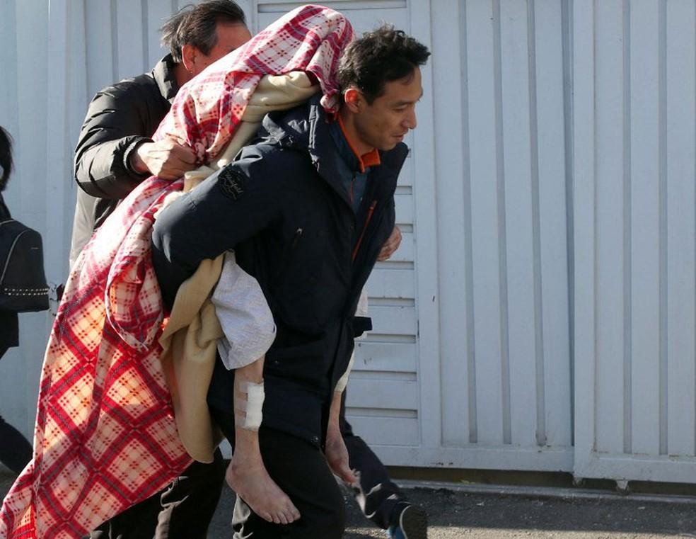 Homem socorre paciente de hospital que sofreu incêndio nesta sexta-feira (26)  (Foto: Yonhap / AFP)