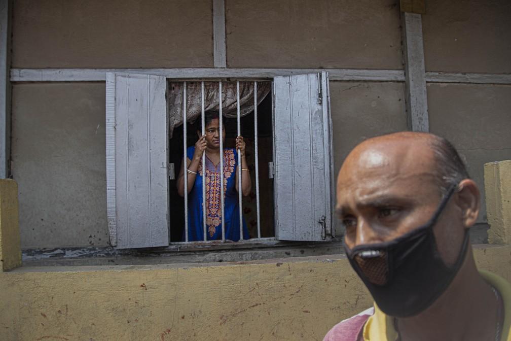 Mulher observa homem desinfectando rua em Gauhati, na Índia, neste domingo (5) — Foto: Anupam Nath/AP