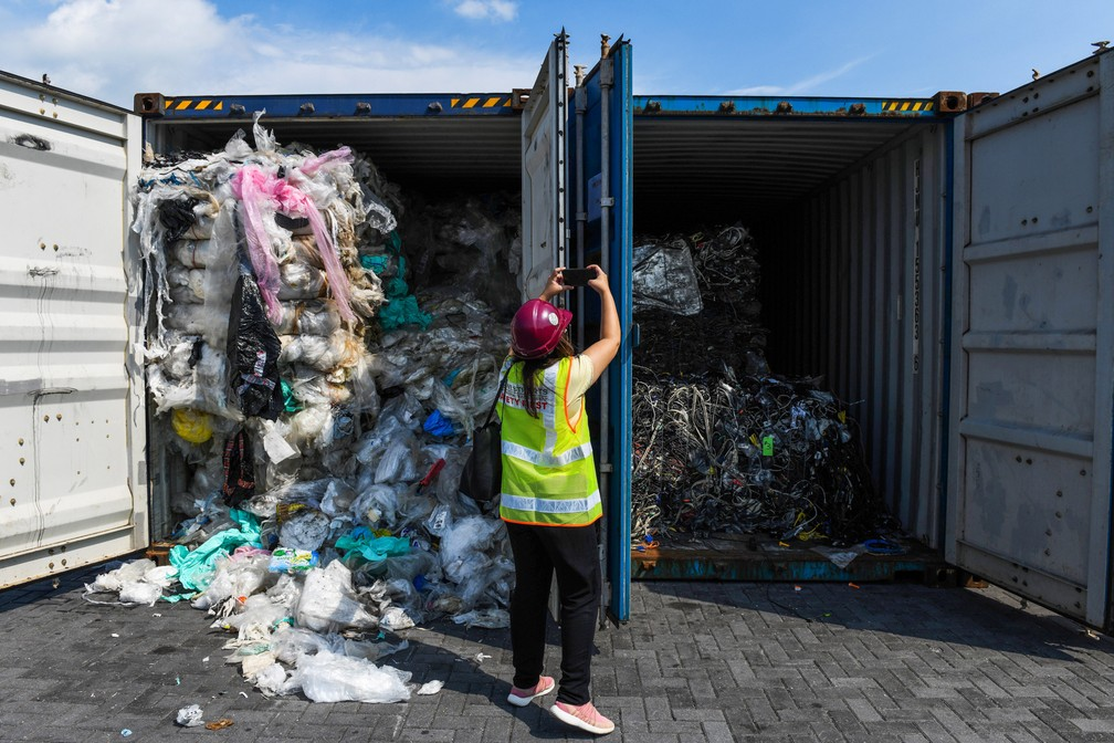 Uma mulher tira fotos de depósitos de lixo cheios de plástico antes de enviá-los de volta ao país de origem em Port Klang, a oeste de Kuala Lumpur, na Malásia — Foto: Mohd Rasfan/AFP