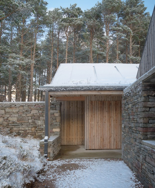 Pedras e madeira se misturam no exterior da casa (Foto:  Richard Fraser/ Deezen/ Reprodução)