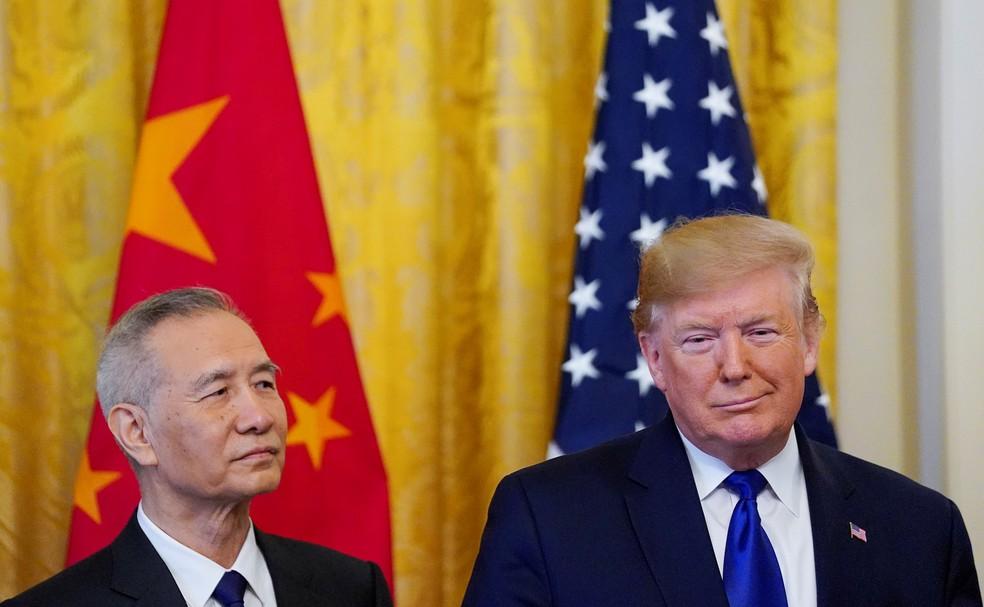 O vice-primeiro-ministro chinês, Liu He, e presidente dos EUA, Donald Trump, assinam a primeira fase de um acordo comercial — Foto: Reuters