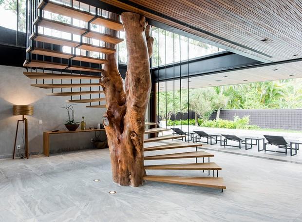 A escada Carvalho, produzida por Hugo França a partir de um tronco caído, ganhou lugar de destaque na casa de praia projetada pelo arquiteto Anderson Muniz (Foto: André Godoy/Divulgação)