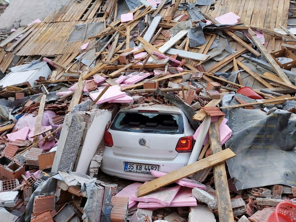 Carro fica encoberto por escombros de prédio em Izmir, Turquia, que desabou após terremoto nesta sexta (30) — Foto: Tuncay Dersinlioglu/Reuters