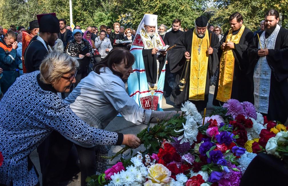 Mulheres depositam flores durante cerimônia religiosa em memória às vítimas do ataque a escola na Crimeia — Foto: Andrey Petrenko/ AFP