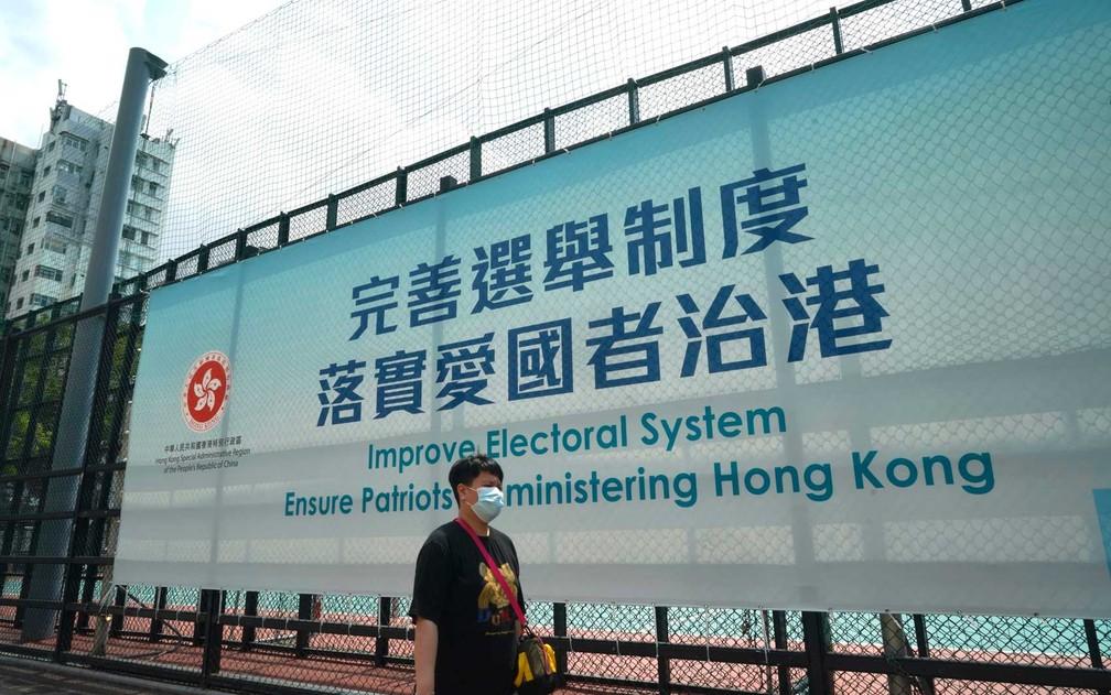 Homem passa por anúncio do governo sobre a reforma do sistema eleitoral de Hong Kong — Foto: Kin Cheung / AP Photo