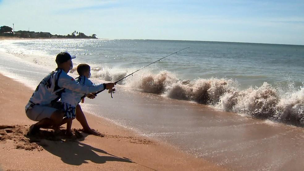 Osvaldo e o filho Bernardo, de 3 anos, pescam na praia de Carapebus, na Serra — Foto: Reprodução/TV Gazeta