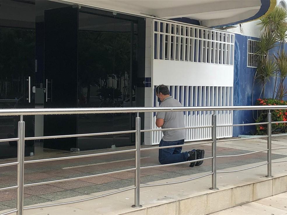 De joelhos, Mardônio reza em frente a hospitais de Sobral. — Foto: Mateus Ferreira